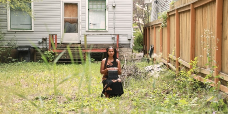 Liz Ikiriko's Homegoing, a 2017 colour photograph of a woman sitting in a yard holding a box.